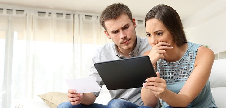 A young couple analysing their budget before buying their first home.