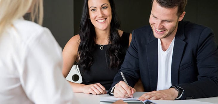 A young couple signs their settlement paperwork after buying their first home.