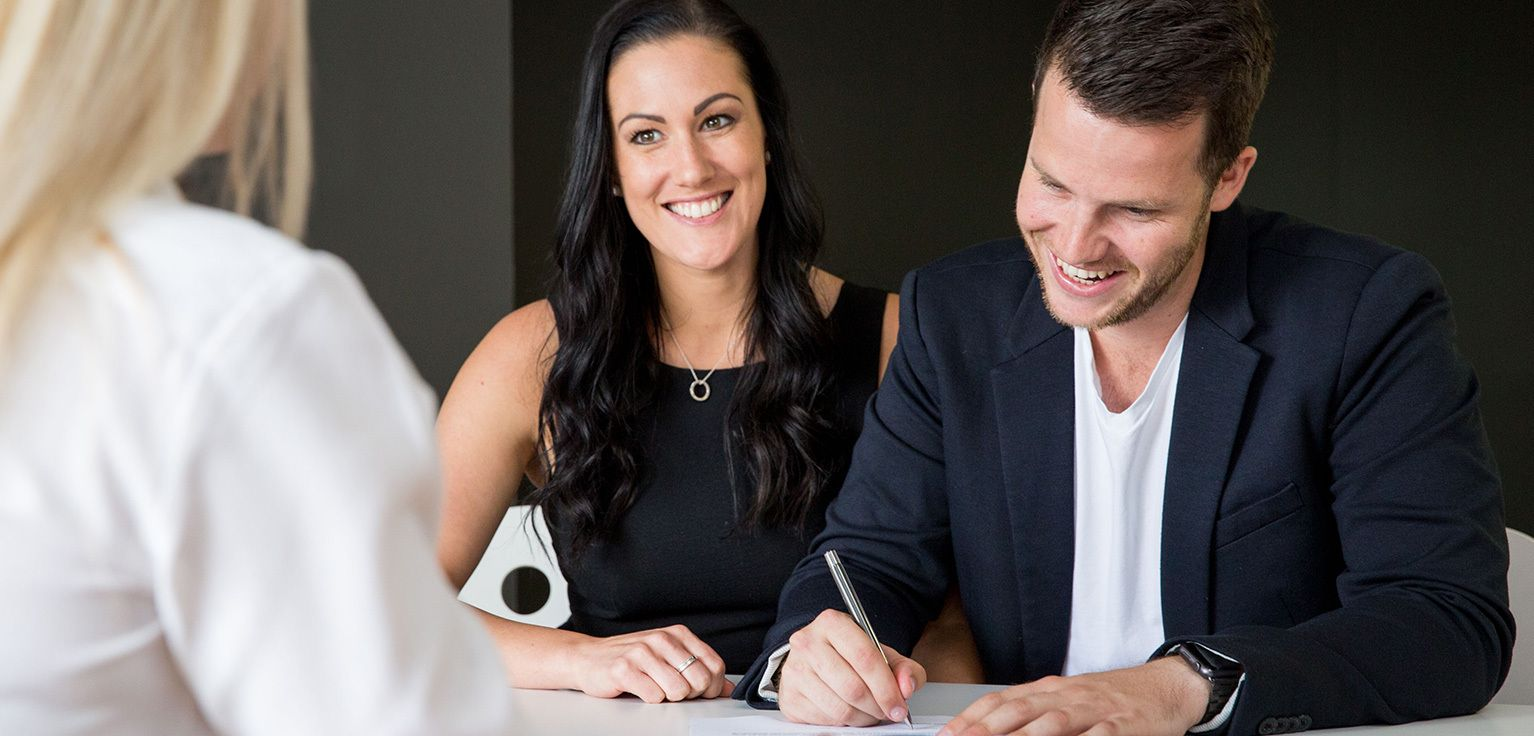 A young couple signing documents during a conveyancing transaction.